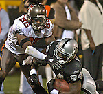 Tampa Bay Buccaneers defensive back Brian Kelly (25) tackles Oakland Raiders wide receiver Jerry Porter (84) on Sunday, September 26, 2004, in Oakland, California. The Raiders defeated the Buccaneers 30-20.