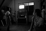 Young sex workers wait for customers in a Mae Sot Karaoke Bar/Brothel. Mae Sot is a town in western Thailand and is the main land gateway between Thailand and Burma. It is a notable trade hub and has a substantial population of Burmese refugees and economic migrants. As a result it has also gained notoriety for its trade in gems and teak, as well as black market services such as people trafficking and drugs.Each day hundreds of Burmese cross the Moi River into Thailand to trade, search for work, or escape both an oppressive Military regime and poverty. Either officially across the Friendship Bridge (linking Mae Sot with Myawaddy in Myanmar) or unofficially by crossing the Moi river using whatever means are possible to them.