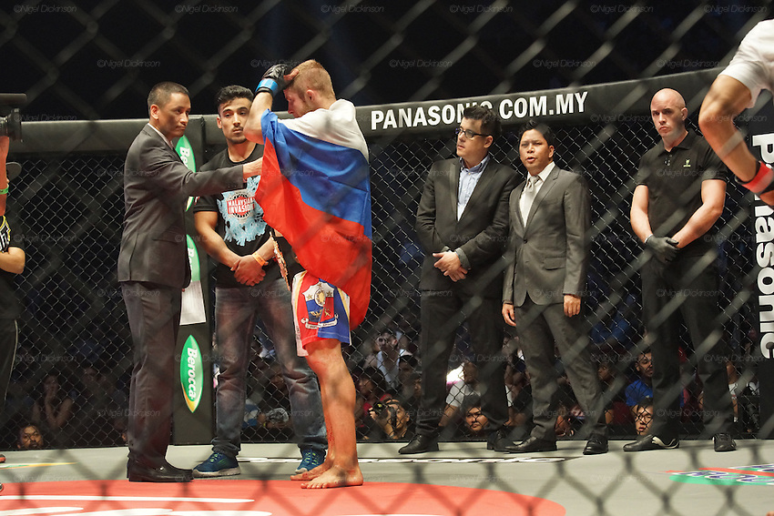 CEO of ONE Victor Cui stands between judges behind. The winner Russian Vitaly Bigdash, draped with flag, Top middleweight champion beats the reigning champion Igor Svirid, One middleweight world champion from Kazakstan<br /><br />MMA. Mixed Martial Arts &quot;Tigers of Asia&quot; cage fighting competition. Top professional male and female fighters from across Asia, Russia, Australia, Malaysia, Japan and the Philippines come together to fight. This tournament takes place in front of a ten thousand strong crowd of supporters in Pelaing Stadium. Kuala Lumpur, Malaysia. October 2015