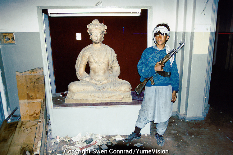 A sculpture of Buddha and is young Mujahidin bodyguard, in charge of the security of the National Museum in 1995.Under the Rabani and Massoud government in 1992-1996, the National Museum was  completely loot and destroy. Kabul, Afghanistan.