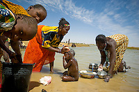 A woman washes her child in the Niger River as another woman washes pots and pans, in the town of Gao. /Felix Features