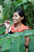 A malaysian girls smelling wild ginger while standing next to the plant, Sepilok, Sabah