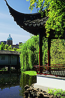A pagoda resting spot with benches in the public park at Dr. Sun Yat Sen Classical Chinese Garden and Park, with the Sun Tower in the background, Chinatown, Vancouver, BC.