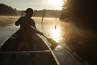 Woodford, VT, USA - August 23, 2008: A girl paddles a canoe on a beaver pond in atop the Green Mountains of southern Vermont as the early morning mist rises with the sun.