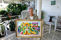 The artist, Alix Roys' sister, Marlene Etienne, at her home. She sadly describes his death in the January 12 earthquake and holds her favorite paintings of his.