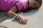 A young injured girl laying hurt on concrete next to a beach