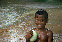 CAMBODIA 2007, BENG MEALEA TEMPLE, BOY IN POURING RAIN WITH PUMPKIN
