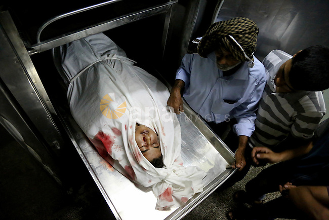 A Palestinian relative mourns over ther body of Mohammed al-Masri, 17, at a hospital morgue, in Beit Lahia in the northern Gaza Strip on July 31, 2015. Al-Masri killed and another wounded after being shot by Israeli gunfire in the northern Gaza Strip Friday near the border fence west of the Beit Lahiya area, a Palestinian medical official said. Photo by Nidal Alwaheidi