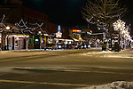 Idaho, North, Coeur d'Alene. Sherman Avenue at night with snow and shops including Hudsons Hamburgers.
