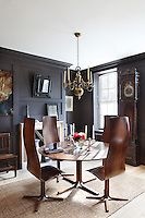 The panelled dining room is furnished with an Arne Jacobsen designed table and chairs