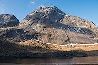 Granite wall of Breiflogtind mountain peak rises over trail to Horsied beach, Moskenesøy, Lofoten Islands, Norway
