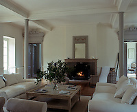Double doors open on either side of the large fireplace in the living room arranged in elegant symmetry to match with pairs of sofas and armchairs