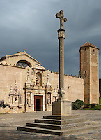 Low angle view of the wall and the baroque facade, entrance to the church, 16th century, with a cross in the foreground, Monestir de Poblet, 1151, Vimbodi, Catalonia, Spain, pictured on May 20, 2006, in the afternoon. The Monastery of Poblet belongs to the Cistercian Order and was founded by French monks. Originally, Cistercian architecture, like the rules of the order, was frugal. But continuous additions  including late Gothic and Baroque, eventually made Poblet one of the largest monasteries in Spain which was later used as a fortress and royal palace. It was closed in 1835 by the Spanish State but refounded in 1940 by Italian Cistercians. It is a UNESCO World Heritage Site. Picture by Manuel Cohen.