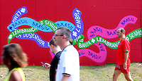 Supporters walk past Brasil grafiti in Salvador, one of the 12 host cities of the 2014 FIFA World Cup