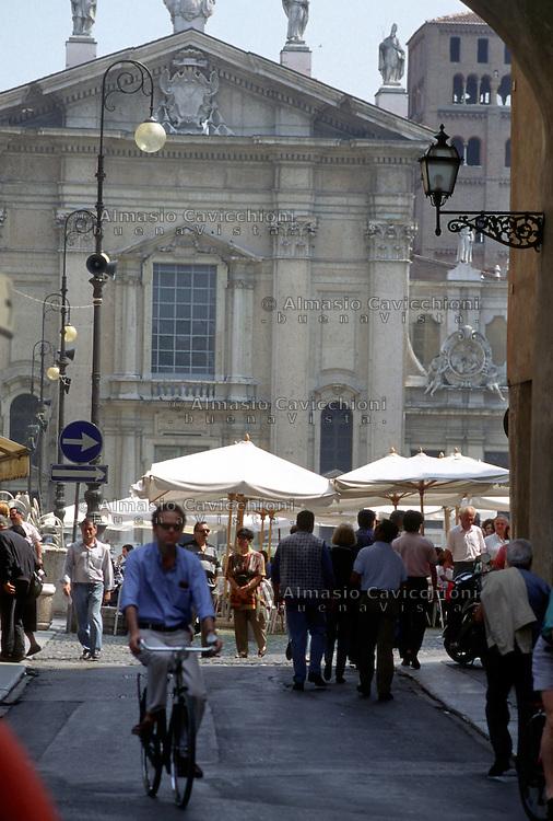 Mantova, gente in bicicletta nel centro storico. In fondo la facciata del Duomo.<br /> Mantua, People cycling in the old town centre. in the background the Cathedral.