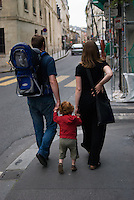 A pregnant woman, her husband and her son walking along the pavemet. The woman is holding her back.