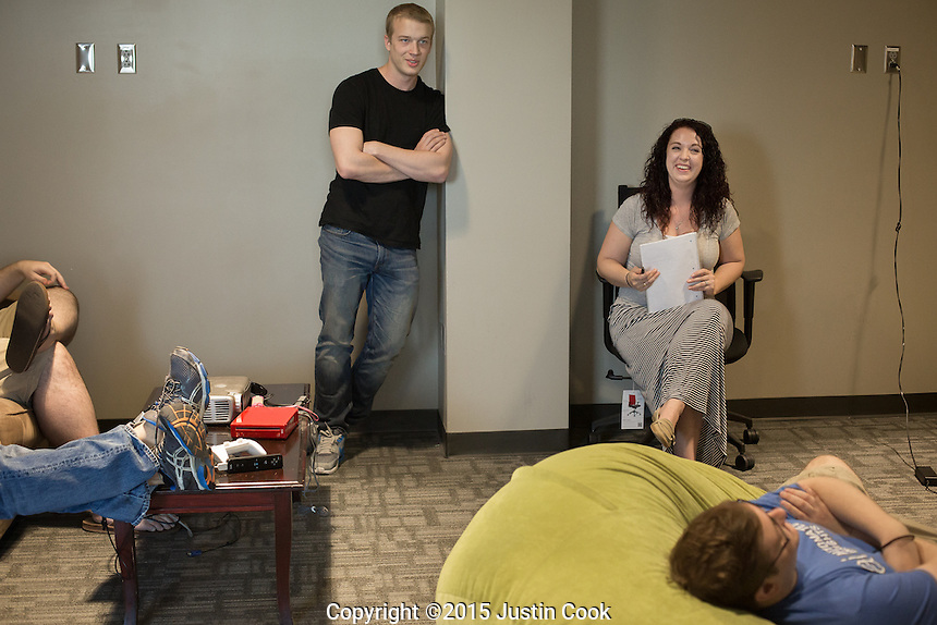 From left: Intern Macon Gambill and Engagement Manager Meagan Palmer and Software Engineer Cole Faloon (on beanbag chair) (ALL CQ) during a meeting at the Automated Insights office in Durham, N.C. on Thursday, May 7, 2015. An Automated Insights algorithm was recently pitted against an NPR reporter to see who could write the best news brief about a Denny's earnings report. (Justin Cook)