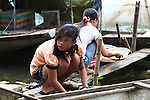 Two girls wash dishes beside a river in Hue, Vietnam. The non-governmental organization, Hearts for Hue, has sponsored a project to relocate riverboat dwellers into permanent housing. Members of Veterans for Peace visited this project during a tour of efforts to mitigate the suffering of Agent Orange victims and victims of bombs and land mines left over from the Vietnam War. April 22, 2013.