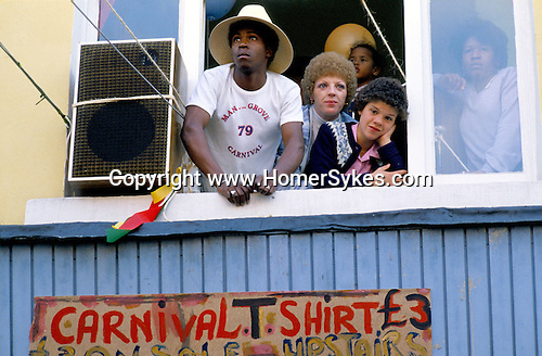 PEOPLE ABOVE THE MANGROVE RESTAURANT LOOKING OUT FROM WINDOW NOTTING HILL CARNIVAL, LONDON, 1979
