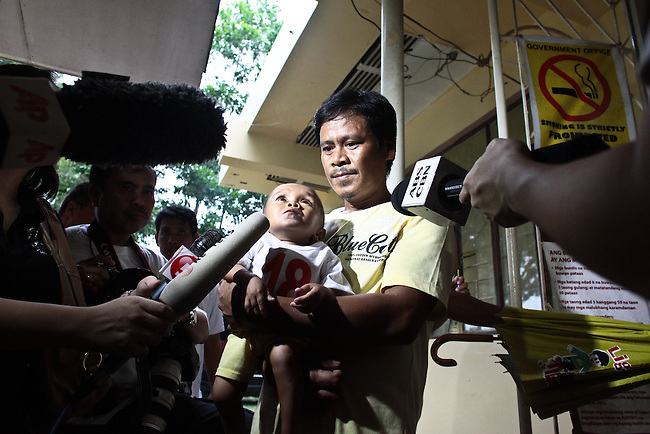 Reynaldo Balawing speaks to reporters in Sindangan, Philippines as he holds his 18-year-old son Junrey, who was officially recognized by Guinness World Records as the world's shortest living man. He is only 23.5 inches tall. June 11, 2011. DREW BROWN/MCT