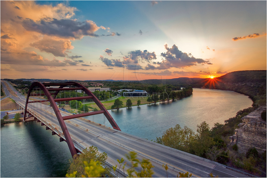 With some afternoon storms in the distance, the sun sets across Austin, Texas and the Texas Hill Country. In the foreground is Pennybacker Bridge, built in 1982, that spans the Texas version of the Colorado River.