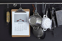 A stainless steel rack against the dark grey wall of the kitchen displays a collection of utensils