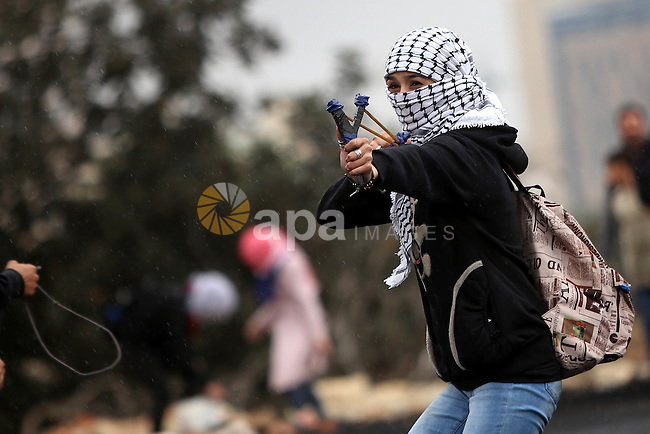 A female Palestinian protester uses a sling shot to throw stones towards Israeli security forces during clashes near the Jewish settlement of Beit El, near the West Bank city of Ramallah October 27, 2015. The current round of violence began last month with clashes at Jerusalem's most sensitive holy site, clashes quickly spread to other areas of east Jerusalem, across Israel and into the West Bank and Gaza Strip. Photo by Shadi Hatem