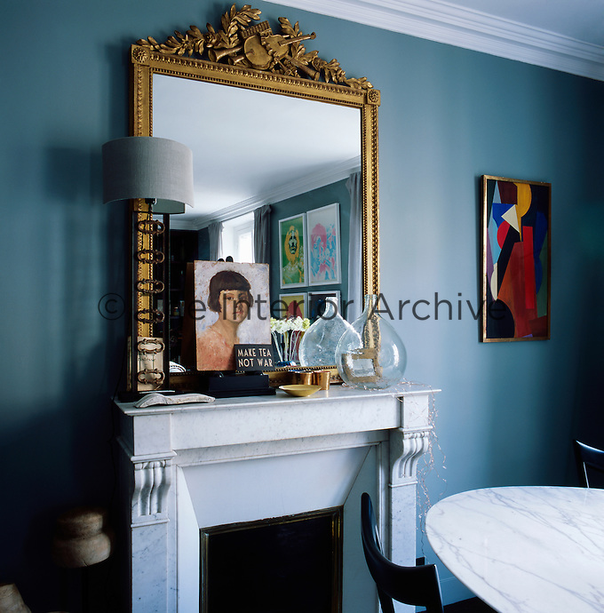 In the informal blue dining room, a gilt mirror  stands on the mantelpiece of the marble fireplace