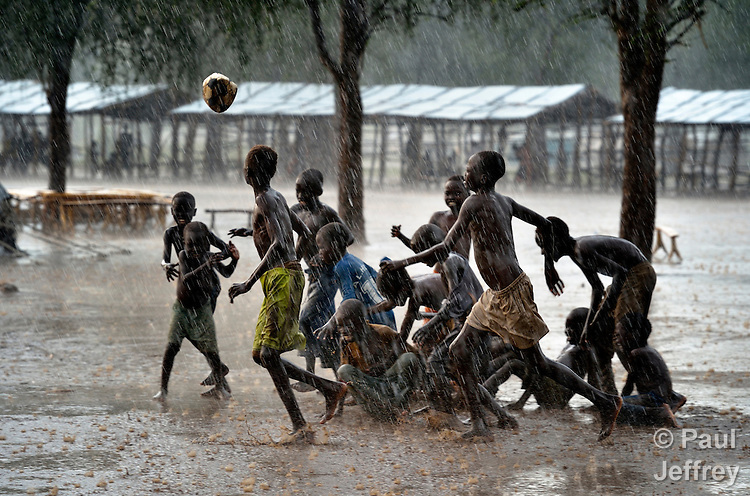 """Children play football during an October 2012 rainstorm in the Doro refugee camp in South Sudan's Upper Nile State. More than 110,000 refugees had come to camps in Maban County from Sudan's Blue Nile region, where the Sudanese military was bombing civilian populations as part of its response to a local insurgency. Under """"informed consent"""" rules that require prior approval, the photographer would have had to stop the boys from playing, have them find and identify their parents somewhere in the sprawling camp, explain the intricacies of """"informed consent"""" and usage, get their signatures, and then return to photograph the game. That's a process that's allegedly designed to assure that the boys are not depicted in an undignified manner. Photo by Paul Jeffrey."""