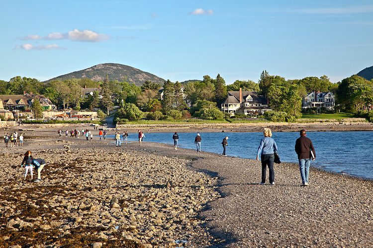 Visitors walk across the exposed gravel bar between the town of Bar Harbor and Bar Island in Acadia National Park, Maine, USA