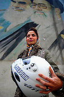 A portrait of Laleh Seddigh with her crash helmet below a billboard depicting Iran's Supreme Leader Ayatollah Ali Khamenei (right) and Ayatollah Khomeini (left). Seddigh is Iran's best female racing car driver.