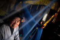 Yan Cheng Shan poses for a portrait while sitting on his bed under mosquito netting in Yi Ling Village, Gangyun County, Jiangsu, China.  Yan Cheng Shan is the grandfather of the orphan Yan Jing Ya (male, 9), whose father died in a coal mining accident and whose mother, who had been purchased for a dowry for marriage from the remote Yunnan province, remarried after the father's death and abandoned the child.  Yan Cheng Shan can no longer support the orphan boy...At the time of the picture, China's Amity Foundation charity, was investigating the family's situation in preparation to raise money to financially support these children and other orphans in similar situations.  With Amity's support, each orphan, aged 6-12, would receive approximately 1,400 RMB annually (about 200 USD) to pay for the cost of living. Amity works to keep children out of the institutional orphanages in China, preferring to provide monetary assistance that can help maintain a family environment for the orphans it helps.