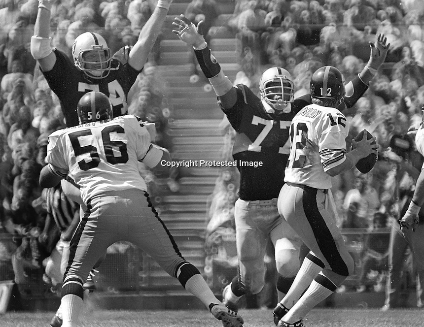 Steelers Terry Bradshaw rushed by Oakland Raiders Dave Rowe, and Charles Philyaw. (1976 photo by Ron Riesterer)