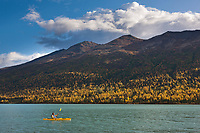 Kayakers Sonny Bartlett, enjoy an autumn day on Eklutna lake, Eklutna lake state park, just north of Anchorage, Alaska.