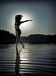 Young woman in swimsuit dancing in moonlight under a full moon in beautiful nighttime nature scenery. Muskoka, Ontario, Canada.