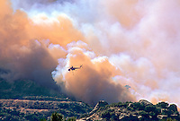870000373 a los angeles county fire fighting helicopter flies above a burning hillside in the path of the topanga fire in the hills above the san fernando valley in southern california