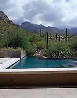 The swimming pool at the rear of the house has been carved from the surrounding rugged Arizona landscape