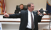 Prince William County (Virginia) assistant commonwealth attorney Richard Conway, points to sniper suspect John Allen Muhammad as he holds the Bushmaster rifle used in the shootings during his closing arguments in the Virginia Beach Circuit Court in Virginia Beach, Virginia on November 13, 2003.<br /> Credit: Steve Earley - Pool via CNP