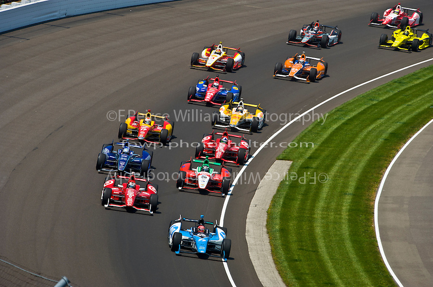 After a restart Simon Pagenaud (#77) leads Scott Dixon (#9), Alex Tagliani (#98), Michel Jourdain, Jr. (#30), Dario Franchitti (#50), Sebastian Saavedra (#17), Ryan Hunter-Reay (#28), Graham Rahal (#38), Charlie Kimball (#83) Helio Castroneves (#3), J. R. Hildebrand (#4), Josef Newgarden (#67) and Justin Wilson (#18) through turn one.