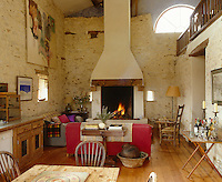 A massive fireplace takes up the far wall of this living area where sitting room, dining room and kitchen occupy the space of an erstwhile barn