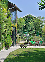 The exterior of a house covered with a mass of foliage from climbing plants clinging to the wall. Two green chairs are set out on a paved terrace area.