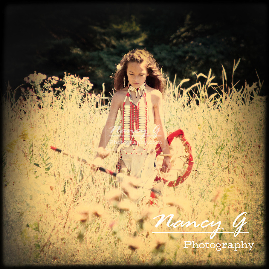 A Native American Indian boy with spear and shield walking through the prairie grasses
