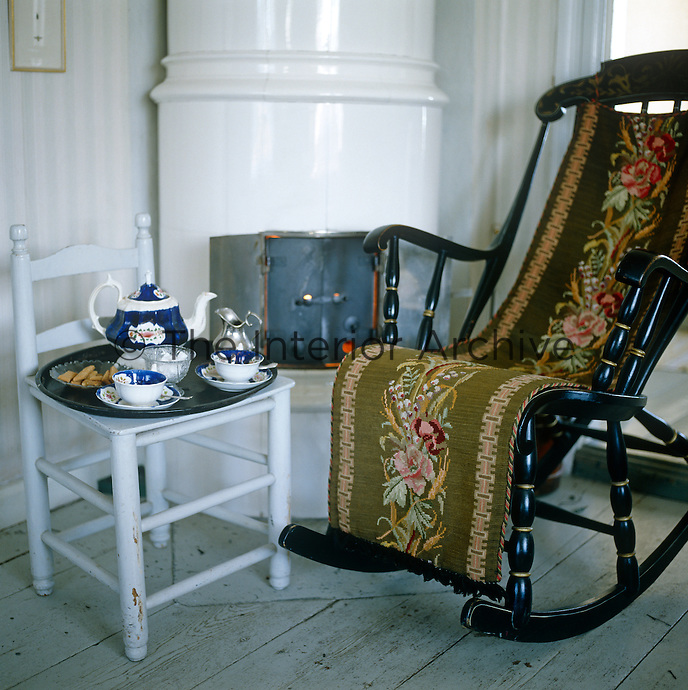 In a corner of this living room next to the ceramic stove a tray is laid with an old-fashioned china tea service, while an antique tapestry runner covers the rocking chair