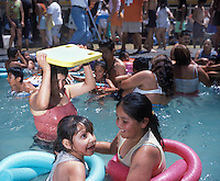 Two girls play in a crowded pool at one of 4 Urban beaches recently inaugarated in Mexico City, as many as the beaches consist of swimming pools, 120 tons of sand, volleyball courts, industrial fans to mimic the wind, they are free and enourmously popular, as many as 4000 people (although designed for 3000) line up early in the morning to enjoy its instalations.  Villa Olimpica, Mexico City, Easter Sunday, April 8, 2007
