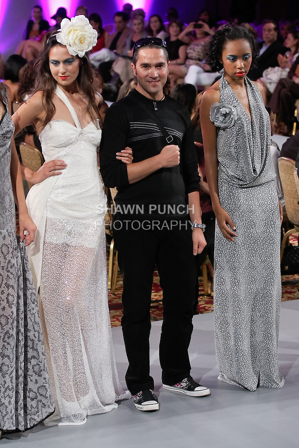 German fashion designer Marco Marcu, walks runway with model at the close of his Haute Couture collection fashion show, during Couture Fashion Week Spring 2012.