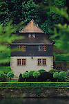 View of house with pointed gables, looking through leaves, showing stags head attached to wall within walled gardens. Mespelbrunn close to Aschaffenburg, Elsava valley. Germany