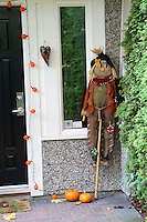 Halloween scarecrow and pumpkins decorating the doorway of a house, Vancouver, BC, Canada