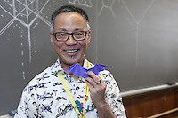 Talo Kawasaki, New York, origami designer and folder, holds a bat model he has created.