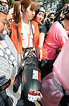 A transvestite sporting a huge strap-on watches the parade during the Kanamara Festival in Kawasaki, Japan. Kanamara means metal phallus, so named after a story dating back hundreds of years in which a local blacksmith made an iron phallus to protect a girl who was thought to be curse. Today, the festival participants are largely prostitutes STDs.