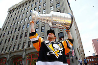 Kris Letang #58 of the Pittsburgh Penguins hoists the Stanley Cup for the crowd during the victory parade in downtown Pittsburgh, Pennsylvania on June 15, 2016. (Photo by Jared Wickerham / DKPS)
